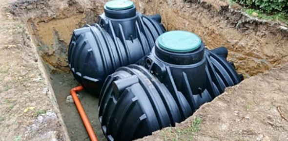 two black water tanks under ground on the backyard